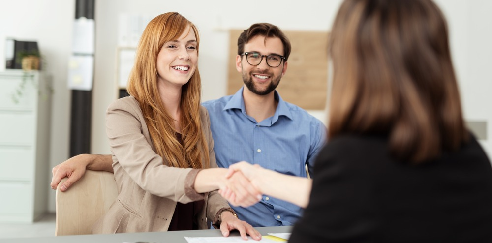 Happy young couple meeting with a broker in her office leaning over the desk to shake hands, view from behind the female agent-1