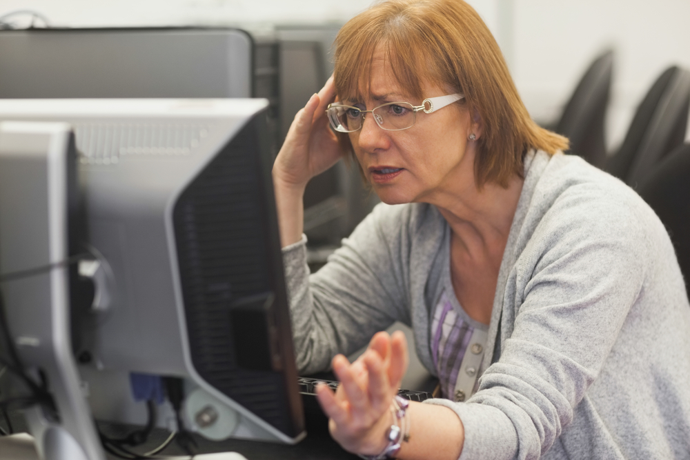 Angry mature student working with computer in computer class